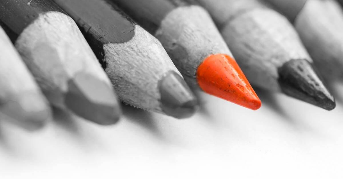 marketing szöveg kiemelkedését jelképező színes ceruza a szürkék között